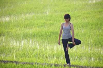 Woman in Yoga pose in a green field