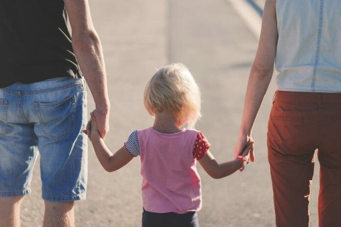 Parents and young daughter walking hand in hand