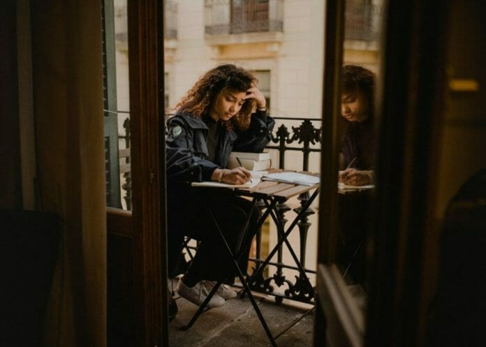 Student on a balcony with books and notes