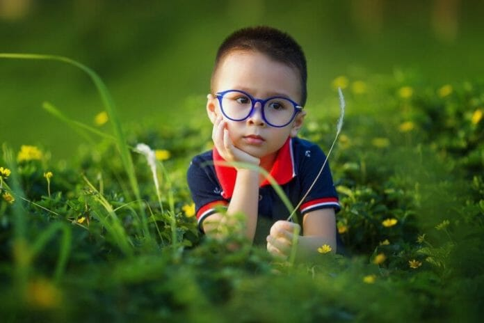 Smart child - boy with glasses in thoughtful pose