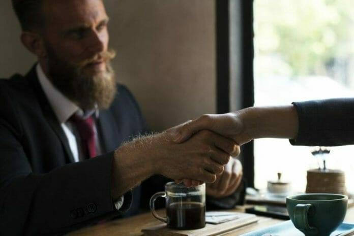 Man shaking another person's hand over coffee